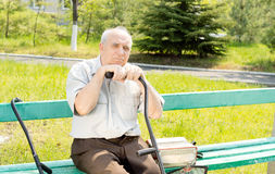 Senior man outdoors. Portrait of senior man sitting on the bench park waiting for someone Royalty Free Stock Photography