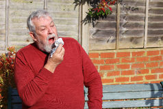 Senior man outside sneezing. Cold. Allergy. Hay fever. Royalty Free Stock Images