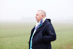 Senior man over foggy field. Middle aged man in black coat and scarf in foggy field Royalty Free Stock Photo