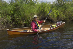 Senior man paddling a small canoe on the Moose River. Stock Images