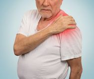 Senior man with pain in his shoulder isolated blue background. Senior man with pain in his shoulder isolated on light blue background Royalty Free Stock Images