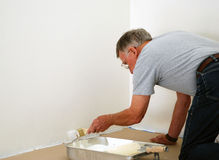 Senior man painting. A senior man painting a wall in white Stock Image