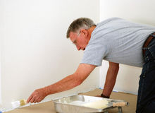 Senior man painting. A senior man painting a wall with a brush Royalty Free Stock Images