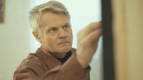 Senior man painting on a canvas. Workshop with pictures stock footage