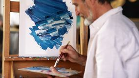 Senior man painting on easel in art class. Man holding a palette drawing abstact picture on canvas stock video