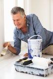 Senior man painting house. Happy senior man decorating house Stock Photography