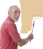 Senior man painting a wall. Active senior man using a roller to paint a wall royalty free stock photo