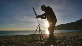 Senior man paints a picture on the beach. Elderly male artist paints standing against raising sun over seashore and. Mountains. Morning sun reflected in the stock video footage