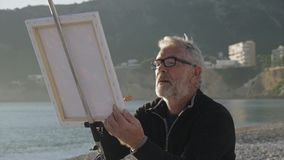 Senior man paints a picture on the beach. Mid shot of elderly male artist in glass painting the canvas at sunset sea stock video footage