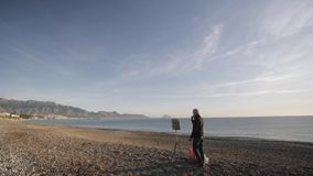 Senior man paints a picture on the beach. Wide shot of elderly male artist sets the picture on the easel on the empty