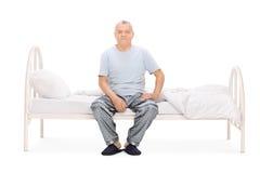 Senior man in pajamas sitting on a bed Royalty Free Stock Photos