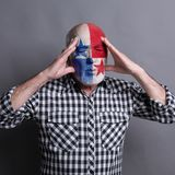 Senior man with Panama flag painted on his face. Portrait of sad senior man with flag of Panama painted on his face. Football or soccer team fan handing head Stock Images