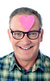 Senior man with paper heart on his forehead Royalty Free Stock Image