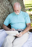 Senior Man in Park With Computer Stock Photography