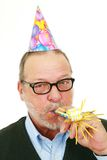 Senior man with party blower Royalty Free Stock Photo