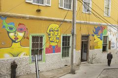 Senior man passes by a colorful graffiti artwork, Valparaiso, Chile. royalty free stock photography
