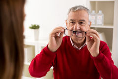 Senior man patient takes glasses aftere change of diopter royalty free stock photography