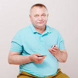 Senior man paying by cell phone over white Royalty Free Stock Image