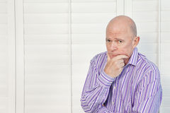 Senior man in pensive mood with hand on chin Stock Images