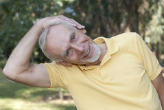 Senior man performing neck stretch Stock Photography