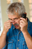 Senior man with phone. Concerned senior man with mobile phone Royalty Free Stock Photos