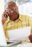 Senior Man On Phone Using Laptop At Home Royalty Free Stock Image