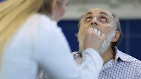 Senior man at the physician checking his throat stock footage