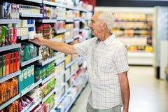 Senior man picking canned food Stock Image