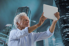 Senior Man picturing himself. Senior business man doing a selfie with tablet PC Royalty Free Stock Image