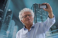 Senior Man picturing himself. Senior Businessman Taking a Selfie in front of a modern city downtown buildings Royalty Free Stock Photos