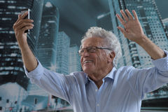 Senior Man picturing himself. Senior Businessman Taking a Selfie in front of a modern city downtown buildings Royalty Free Stock Photo