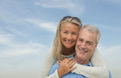Senior Man Piggybacking Woman Against Sky Stock Images