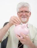 Senior man and piggybank. Senior man holding a piggybank over white Royalty Free Stock Images