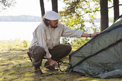 Senior man pitches a tent Royalty Free Stock Photos