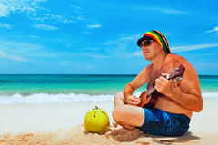 Senior man play reggae on Hawaiian guitar on caribbean beach. Happy retiree age man in funny hat has fun, play reggae music on Hawaiian guitar, enjoy caribbean royalty free stock image