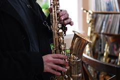 Senior man play saxophone in the party. Close up hand holding the saxophone Royalty Free Stock Image