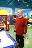 Senior man playing air hockey. In amusement center royalty free stock photos
