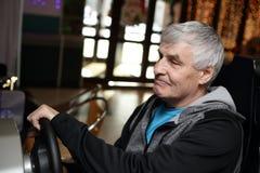 Senior man playing arcade game machine. At an amusement park Stock Photo