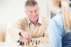 Senior Man Playing Chess With Teenage Granddaughter Royalty Free Stock Image
