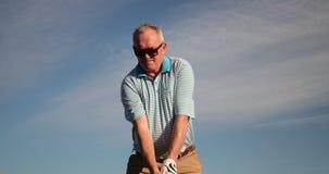 Senior man playing golf. Low angle shot of a senior man swinging a golf club stock video footage