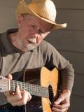 Senior man playing guitar. Senior man with cowboy hat playing a Martin guitar and singing along Royalty Free Stock Images