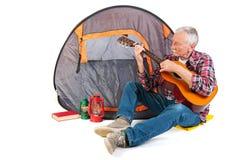 Senior man playing guitar by tent Royalty Free Stock Image
