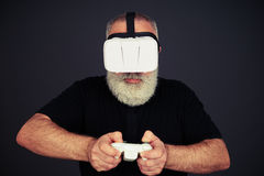 Senior man is playing on the joystick wearing hi-tech VR headset Royalty Free Stock Images