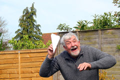 Senior man playing with paper airplane. Stock Photography