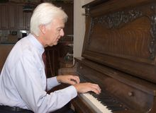 Senior Man Playing Piano. Senior Man Playing an Upright Piano Stock Images