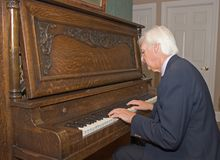 Senior Man Playing Piano. Senior Man Playing an Upright Piano Royalty Free Stock Photos