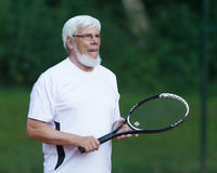 Senior man playing tennis. On a gravel court Royalty Free Stock Images
