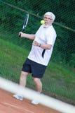 Senior man playing tennis. On a gravel court Stock Image