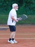 Senior man playing tennis. On a gravel court Royalty Free Stock Photos