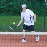 Senior man playing tennis. On a gravel court Royalty Free Stock Image